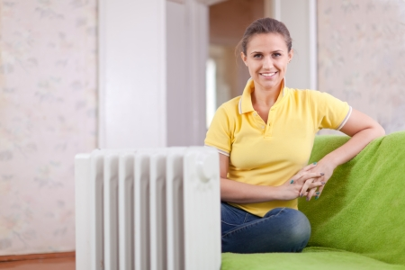 Happy woman near oil heater in home