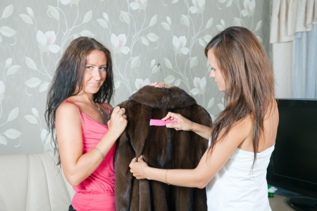 furskin: Two women cleaning fur coat  with whisk broom at home Stock Photo