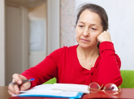 lamentable: serious mature woman reads documents at home