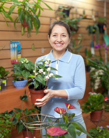 Happy mature woman with Clerodendrum surrounded by different flowers in flower store photo