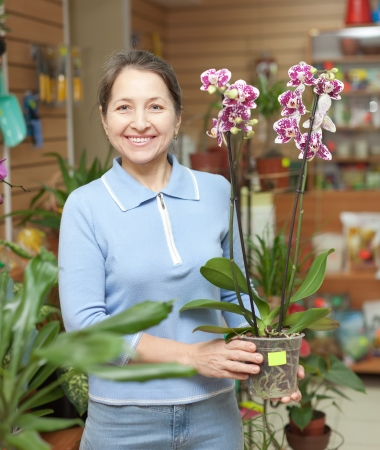 Happy mature woman with Phalaenopsis orchid in pot at flower store photo