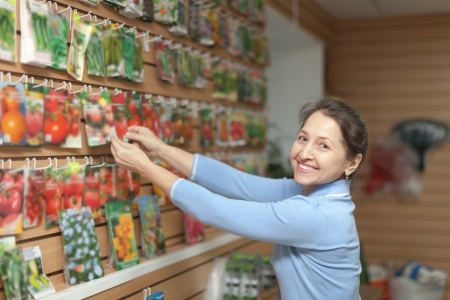 woman chooses the seeds at store for gardener photo