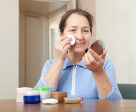 Smiling mature woman cleans the make-up from face Stock Photo - 17767355