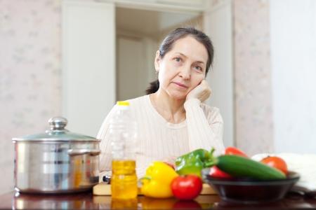 weariness: cansancio madura mujer con verduras en su cocina
