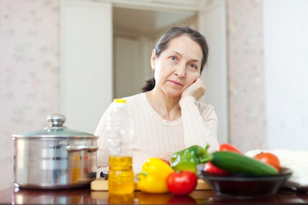 weariness: weariness mature woman with  vegetables at her kitchen