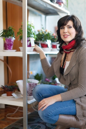 woman in flower shop near the shelves with flower pots Stock Photo - 17825337