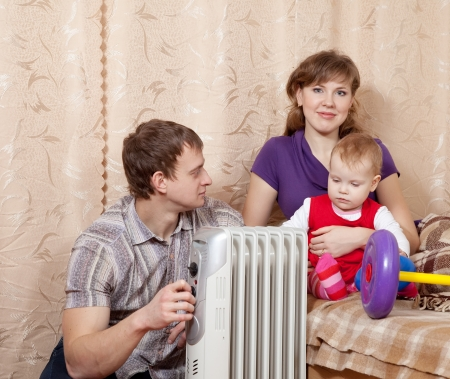 Family  relaxing at home near oil heater
