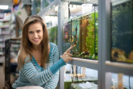 Woman chooses aquarium for fishes in pet-shop  photo