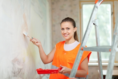 spalpeen: Female house painter paints wall with brush