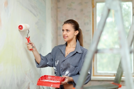 modifying: Happy woman paints wall with roller
