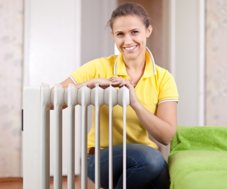 Happy woman near oil heater in home Stock Photo - 17824813