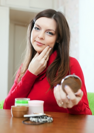 Young woman looks on face in mirror  Stock Photo