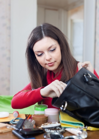 Young woman can not finding anything in her purse at table photo