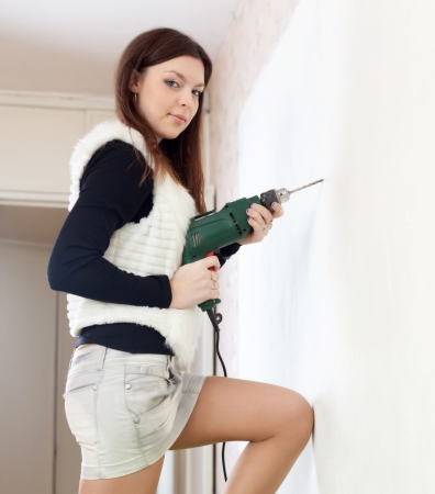 Young woman  drills wall with drill at home Stock Photo - 17878127