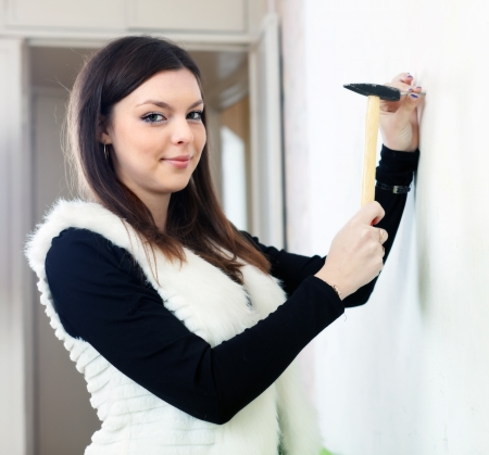 Smiling pretty woman wants to drive nail into wall with hammer   Stock Photo - 17878130