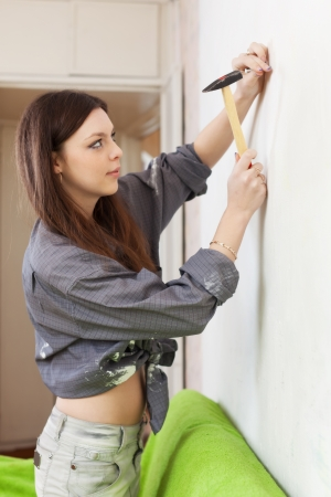 Young woman driving a screw into the wall Stock Photo - 17878128