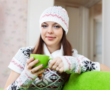 casualy: Pretty girl warms with cup of tea at house in winter Stock Photo