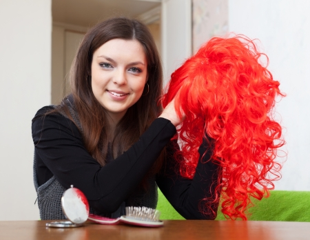 peruke: Young brunette woman with red periwig at home Stock Photo