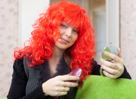 periwig: Woman in red wig with comb and mirror