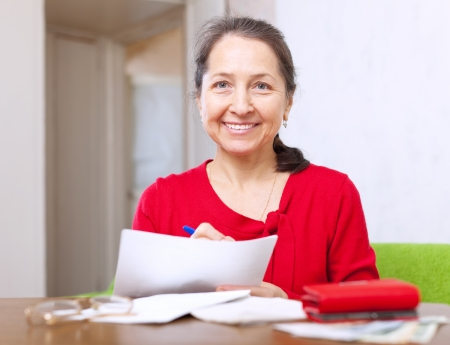 joyful mature woman fills in payment documents at home Stock Photo - 17878686