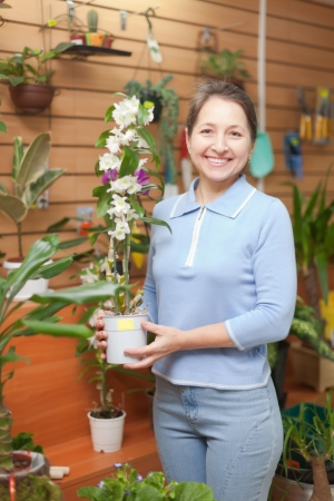 Happy mature woman chooses  orchid  in flower shop photo