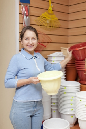 Smiling mature  woman chooses plastic flower pot in the store for gardeners Stock Photo - 17878518