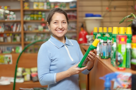 Smiling mature  woman chooses fertilizers at store for gardeners photo