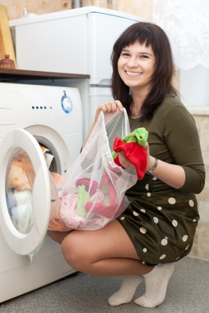 Young housewife loading the washing machine with laundry bag in kitchen Stock Photo - 17887745