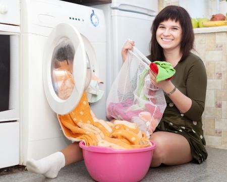 lavando ropa: ama de casa poniendo la ropa en lavadora y mirando a la c�mara