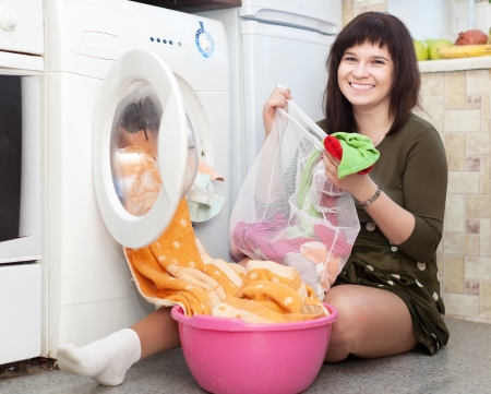 housewife putting clothes into washing machine and looking at camera photo