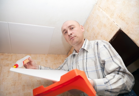 soffit cladding: guy glues ceiling tile at home
