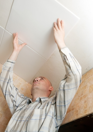 soffit cladding: Man glues ceiling tile at home