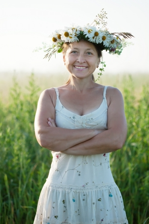 chaplet: Outdoor portrait of  mature  woman in  camomile chaplet