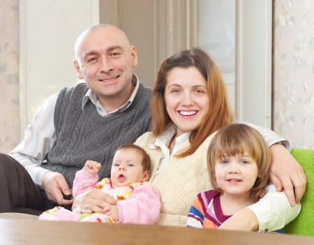 joyful parents with their two kids at home interior Stock Photo - 17887594