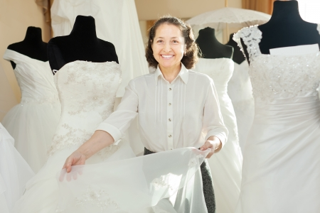 bridal gown: La mujer muestra vestido de novia en la tienda de moda nupcial Foto de archivo