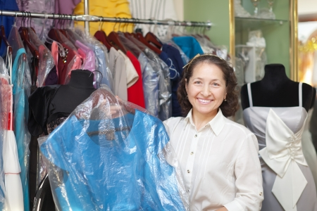Smiling mature woman chooses evening dress at clothing store photo
