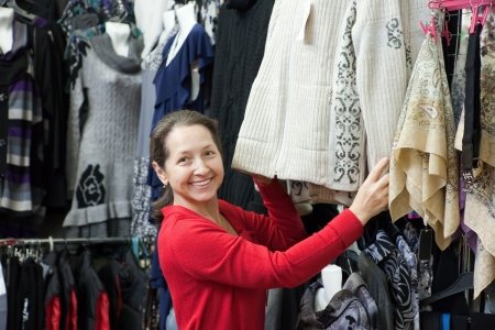 Mature woman  chooses clothes at fashionable shop photo
