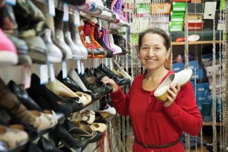 Mature woman chooses shoes at shoes shop photo