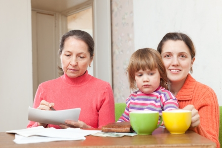 utility payments: grandmother mother fills in utility payments bills at home Stock Photo