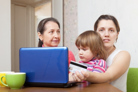 Two women and child shopping online in living room at home photo
