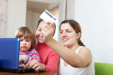 Family of three generations buying online with laptop and credit card  in living room photo
