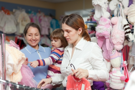 Two women and child chooses clothes at store. Focus on woman photo