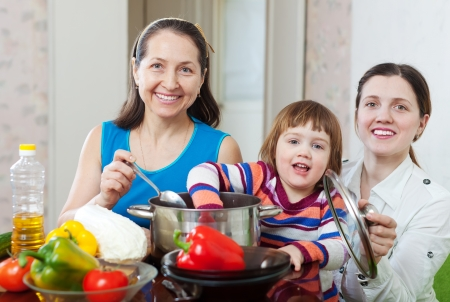 Mature woman and her adult daughter with baby girl cook veggie lunch in kitchen at home Stock Photo - 17926072
