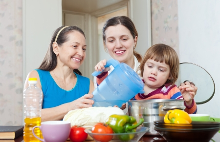 Happy women with child together cooking veggie lunch in kitchen at home Stock Photo - 17926061