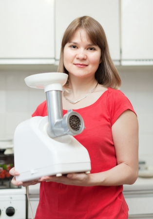 eastward: Woman with electric grinder in kitchen