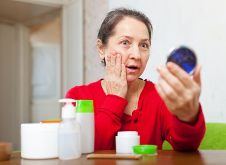 corrugation: emotional mature woman stares on her face in mirror at home