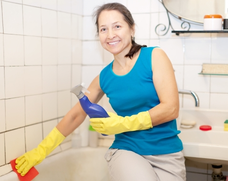 Mature woman cleans bathtub in bathroom   photo