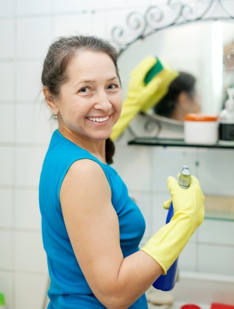 mature woman  cleans  mirror in bathroom at home photo