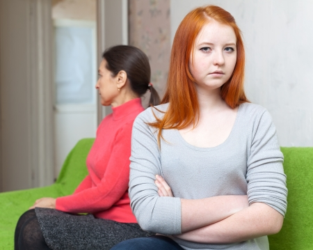 Mature mother and teen daughter having conflict at home. Focus on girl Stock Photo - 18326625