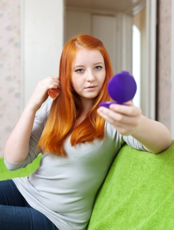 red-haired teen girl combing  hair in home interior photo